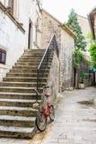 Bici vieja cerca de las escaleras en una calle de la ciudad vieja de Kotor, Montenegro Fotografía de archivo