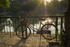 Bici vieja en el pavimento urbano bajo luz del sol brillante de la tarde Imagen de archivo libre de regalías