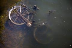 Bici vieja hundida en agua Imágenes de archivo libres de regalías