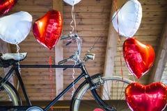Bici vieja que vuela limitada a los globos en forma de corazón Imagen de archivo