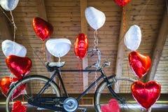 Bici vieja que vuela limitada a los globos en forma de corazón Imagen de archivo libre de regalías