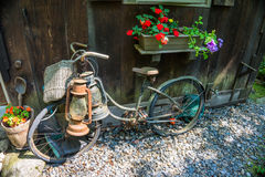 Bici vieja y linternas del vintage que se inclinan contra una casa Foto de archivo libre de regalías