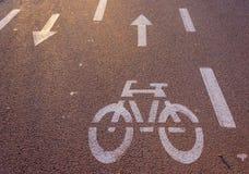 Bici y flecha en el asfalto una puesta del sol Foto de archivo
