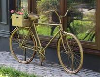 Bici y macizo de flores de bronce Fotos de archivo libres de regalías
