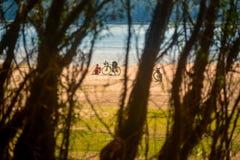 Bici y motorista que descansan sobre la playa del Danubio, Rumania Foto de archivo