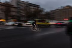 Bicicle rider riding fast in the big city stock photography