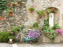 Bicicleta adornada con las flores en Levico Terme, un pueblo en las montañas italianas Imagenes de archivo