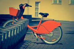 Bicicleta anaranjada en un soporte en ciudad fotografía de archivo