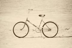 Bicicleta antigua en la playa - sepia retra Imagenes de archivo