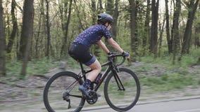 Bicicleta apta nova da equitação da mulher no parque Sun atrav?s das ?rvores Siga o tiro filme