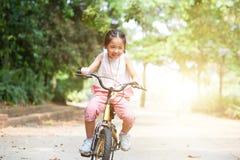 Bicicleta asiática activa del montar a caballo del niño al aire libre fotos de archivo libres de regalías