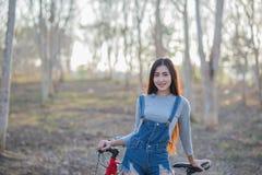 Bicicleta asiática joven y hermosa del montar a caballo de la mujer al aire libre en parque Imágenes de archivo libres de regalías