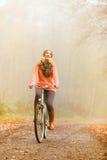 Bicicleta ativa da equitação da mulher no parque do outono Imagens de Stock Royalty Free