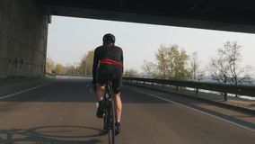 Bicicleta atlética apta del montar a caballo del ciclista Detr?s siga el tiro Entrenamiento joven del jinete de la bici en la bic metrajes