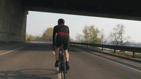 Bicicleta atl?tica apta del montar a caballo del ciclista Detr?s siga el tiro Entrenamiento joven del jinete de la bici en la bic almacen de metraje de vídeo