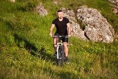 Bicicleta atrativa da equitação do ciclista no prado com as pedras no campo Foto de Stock