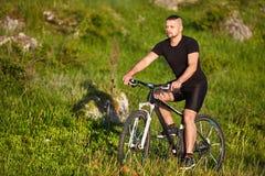 Bicicleta atrativa da equitação do ciclista no prado com as pedras no campo Imagem de Stock Royalty Free