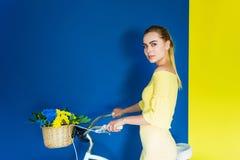 Bicicleta atrativa da terra arrendada da moça com as flores na cesta no azul foto de stock