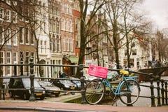 Bicicleta azul con la cesta del silbido de bala en Amsterdam fotografía de archivo