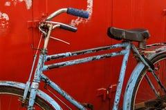 Bicicleta azul do vintage no fundo vermelho Foto de Stock