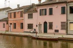 Bicicleta, barco e casas velhas no distrito de san Pietro, Comacchio, AIE fotografia de stock