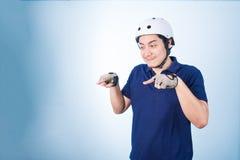 Bicicleta biking del gesto asiático del individuo, con el casco de la bicicleta y los guantes Fotos de archivo libres de regalías