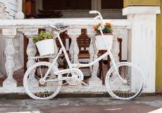 Bicicleta blanca con la cesta hermosa de la flor Imagenes de archivo
