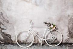 Bicicleta blanca decorativa con la cesta de flores rosadas Imagenes de archivo