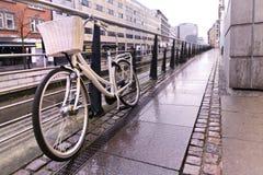 Bicicleta blanca en la calle Amanecer en una ciudad moderna Imágenes de archivo libres de regalías