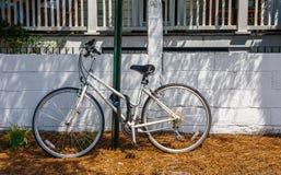 Bicicleta blanca vieja encadenada para poner verde a poste Imagen de archivo