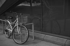 Bicicleta blanco y negro que se inclina contra una verja Fotos de archivo