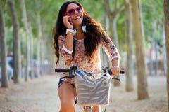 Bicicleta bonita da equitação da moça e fala no telefone Imagem de Stock Royalty Free