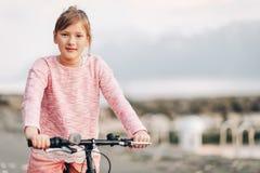 Bicicleta bonita del montar a caballo de la muchacha del niño al lado del lago Foto de archivo