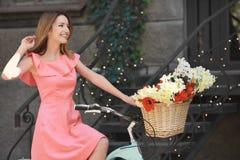Bicicleta bonita nova da equitação da menina com as flores na cesta Imagens de Stock