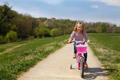 Bicicleta bonito da equitação da menina exterior Fotos de Stock Royalty Free