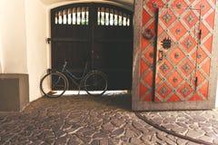 Bicicleta cerca de la vieja puerta del castillo Foto de archivo libre de regalías