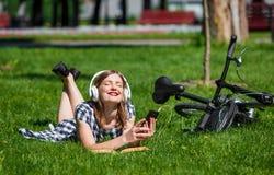 Bicicleta cercana relajante de la mujer joven en el parque Fotografía de archivo