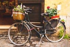 Bicicleta clásica adornada con las plantas parqueadas delante de una puerta de la tienda con tonos suaves y calientes foto de archivo