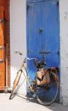 Bicicleta contra puerta azul fotos de archivo