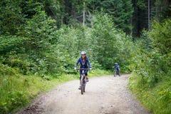 Bicicleta da equitação da jovem mulher na floresta da montanha Imagem de Stock