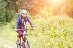 Bicicleta da equitação da jovem mulher na floresta da montanha Imagens de Stock