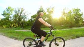 Bicicleta da equitação da jovem mulher no parque verde vídeos de arquivo