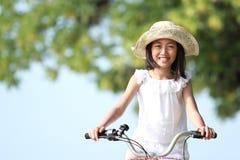 Bicicleta da equitação da menina ao ar livre fotografia de stock