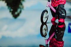 Bicicleta da equitação da menina na poça da água Fotografia de Stock Royalty Free
