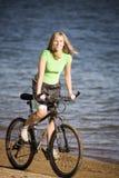 Bicicleta da equitação da mulher na praia fotografia de stock royalty free