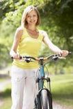 Bicicleta da equitação da mulher no campo Fotografia de Stock