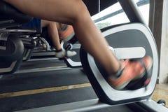 Bicicleta da equitação do exercício da mulher no fitness center imagem de stock