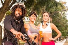 Bicicleta da equitação do homem negro e duas fêmeas desportivas Árvores e trajeto fotos de stock royalty free