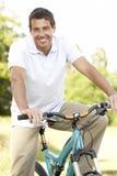 Bicicleta da equitação do homem novo no campo Fotos de Stock Royalty Free