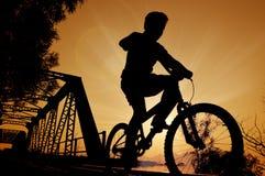 Bicicleta da equitação do menino da silhueta, por do sol Fotografia de Stock